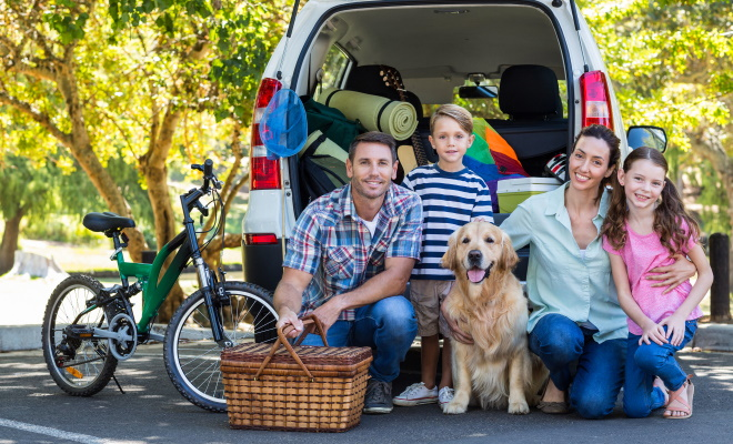 family of four standing behind van with dog